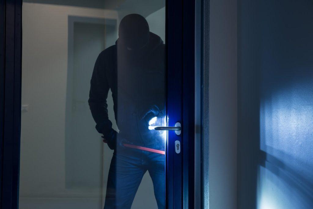 Burglar trying to break in through a security door